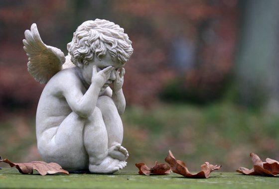 Trauernde Engel aus Stein sitzend, am Boden Herbstblätter